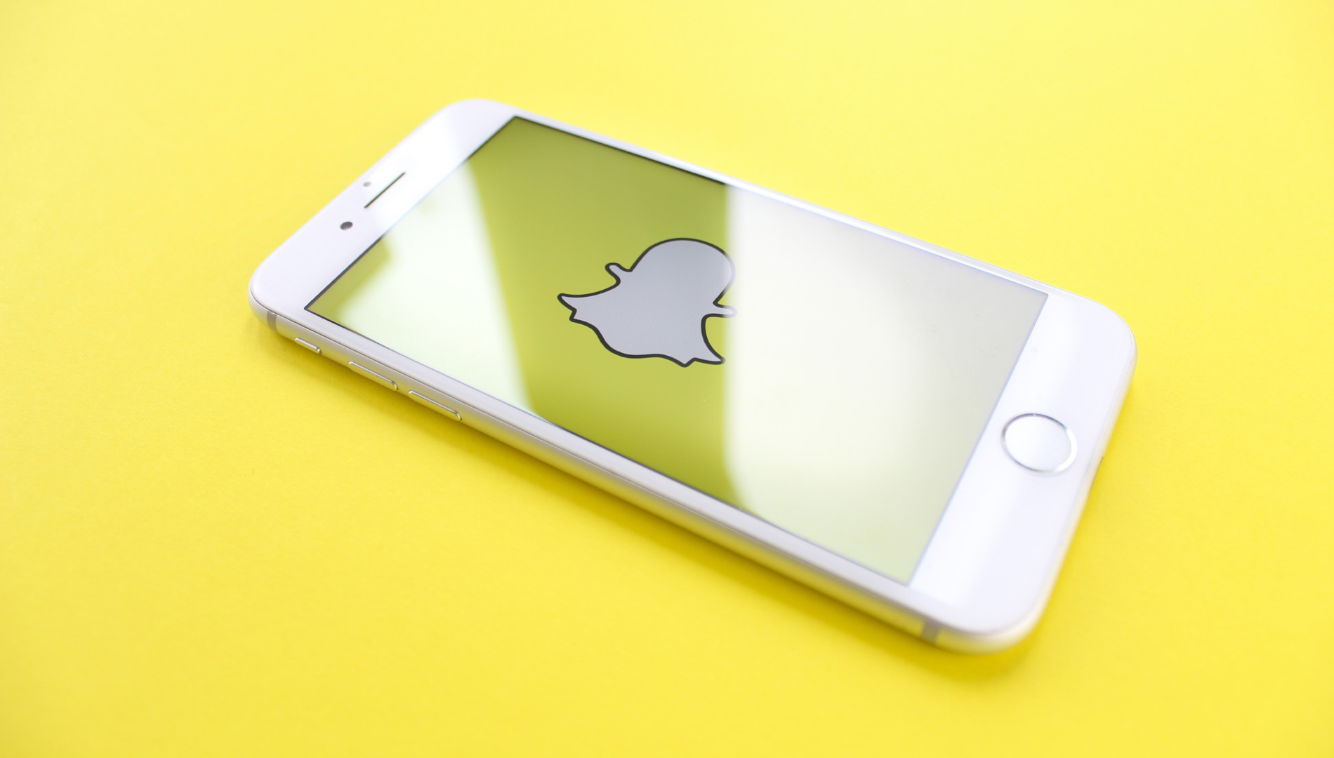 silver iPhone 6 on top of yellow wooden surface showing Snapchat